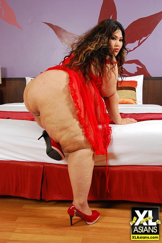 Жирная толстуха показывает свое тело в складках, нарядившись в красное одеяние, и принимая разные позы
