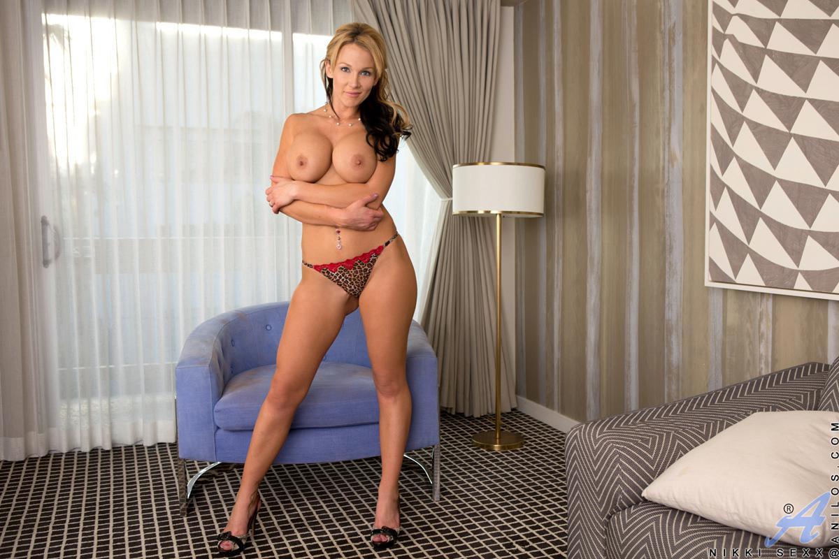 Очеровательная грудастая блондинка Nikki Sexx снимает эротическое платье и позирует обнаженной в кресле