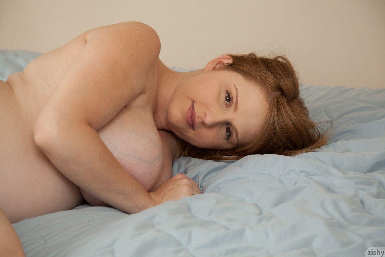 Рыжеволосая беременная девушка красиво позирует перед камерой, демонстрируя свое красивое тело
