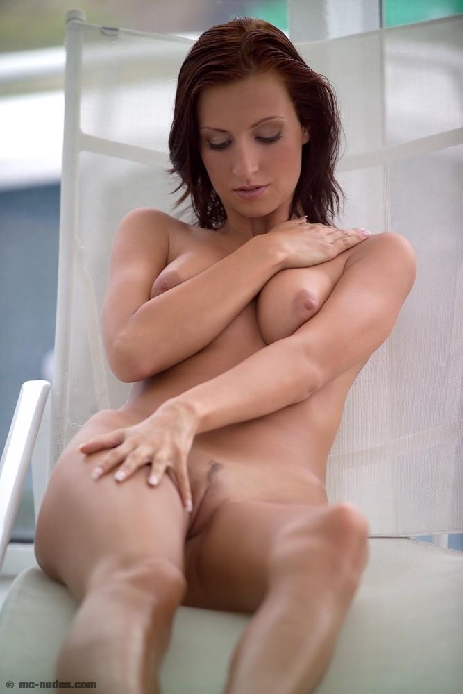 Горячая брюнетка Claudia Cova стоит давая своему голому телу загореть на солнце