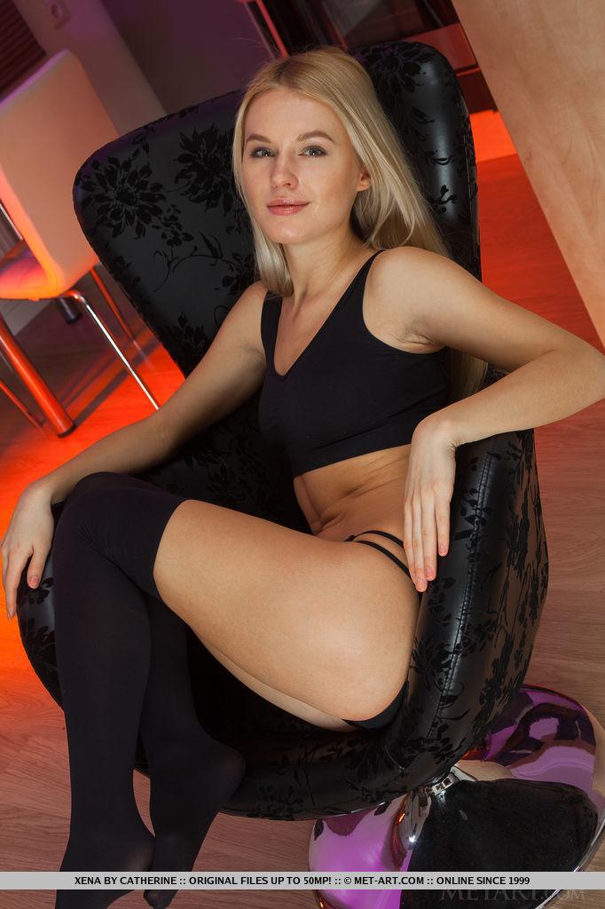 Голая худышка разлеглась на черном кресле в своей комнате