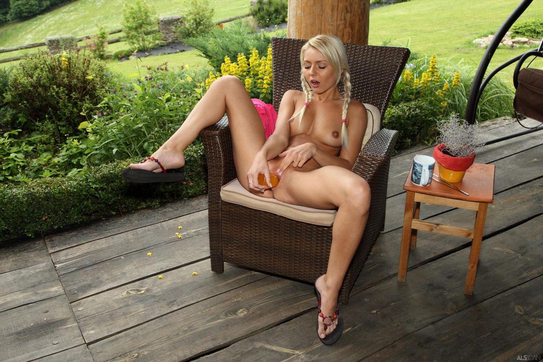 Бритая киска горячей блондинки Pinky June с большими губами раздвигает ноги и трахает себя большой игрушкой на природе