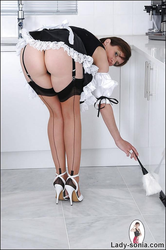 Грудастая мамочка в костюме домработницы показывает свое тело на кухне