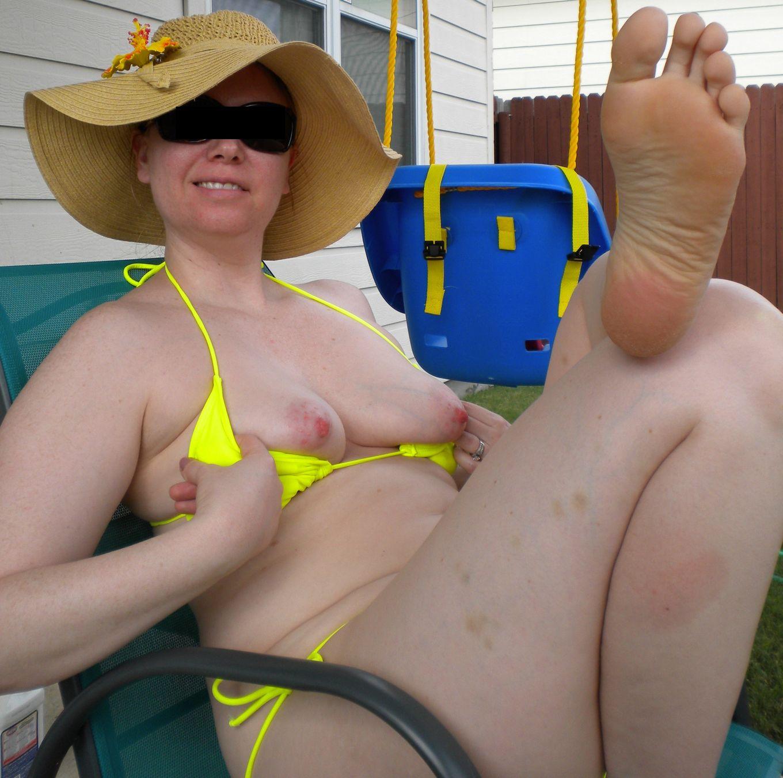 Женщина в ярком бикини показывает сиськи и писает на заднем дворе